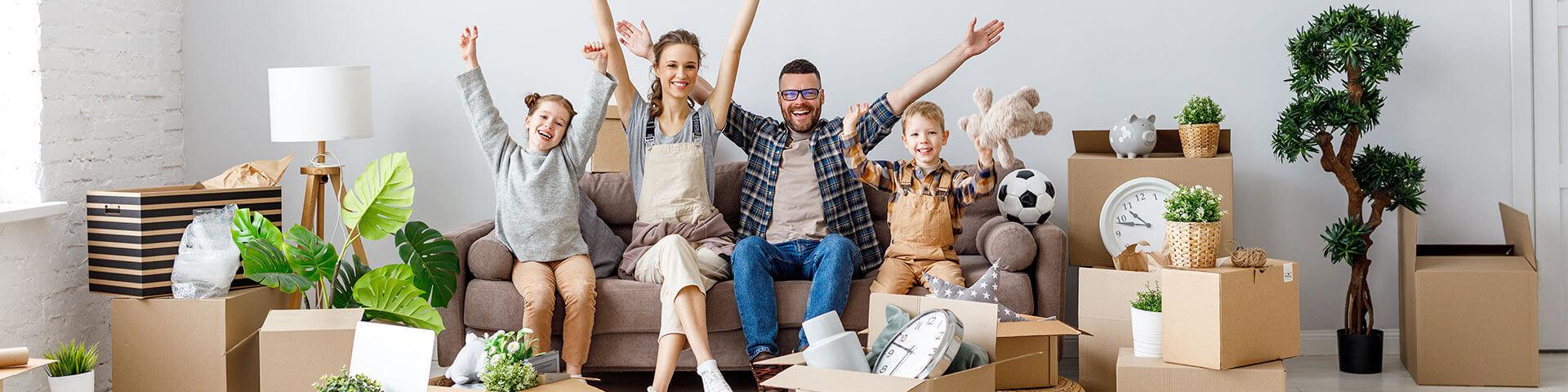 glückliche Familie sitzt auf Sofa mit Umzugskartons im Raum verteilt